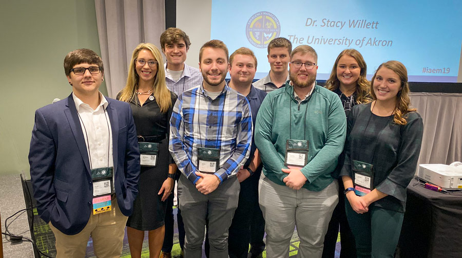 A professor stands with her emergency management students