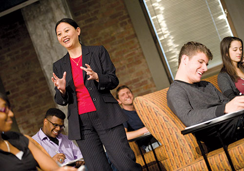 A faculty member in the business school enjoys a light moment with students.