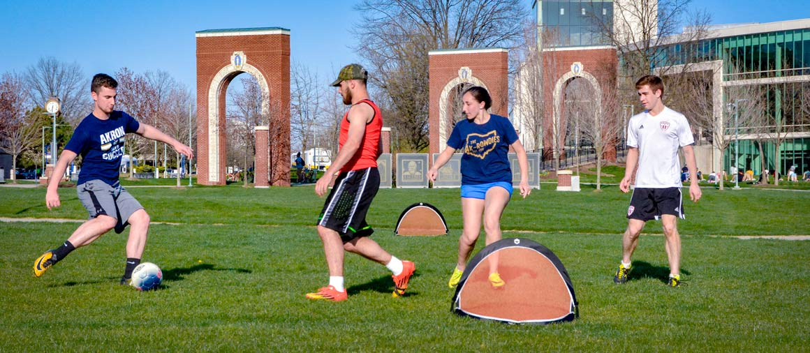 Students playing soccer on Coleman Common on The University of Akron campus