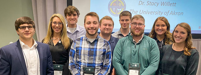 A group of students with their professor at a conference