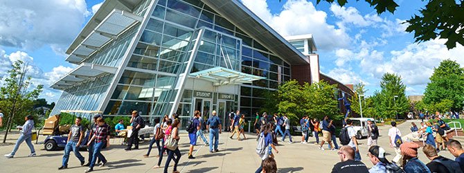 Students walk by the modern student union on a sunny summer day