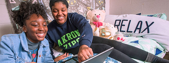 Two students on a bed in a dormatory laughing at someting on a laptop