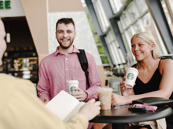 Two students share a laugh in a campus coffeehouse.