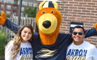 Zippy with two students wearing Akron pride shirts