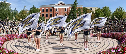 The marching band plays in the center of campus on a sunny day