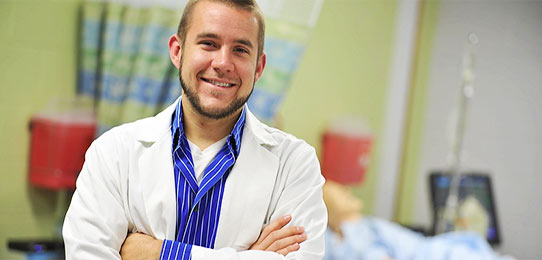 Student in white lab coat poses for a photo during a high school summer college visit day.