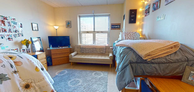 A bright residence hall room with a couch, desk, tv and bed.