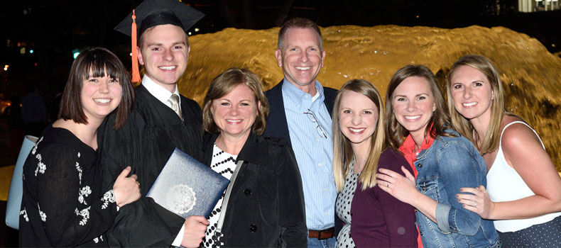 Family of UA college graduate in a group photo at commencement ceremony