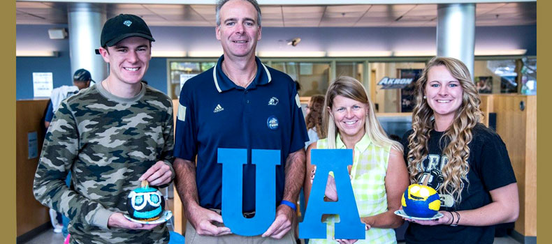 Sibling and parents of college student stand with her holding large blue letters that spell UA