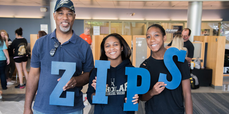Parents of college student stand with her holding large blue letters that spell ZIPS
