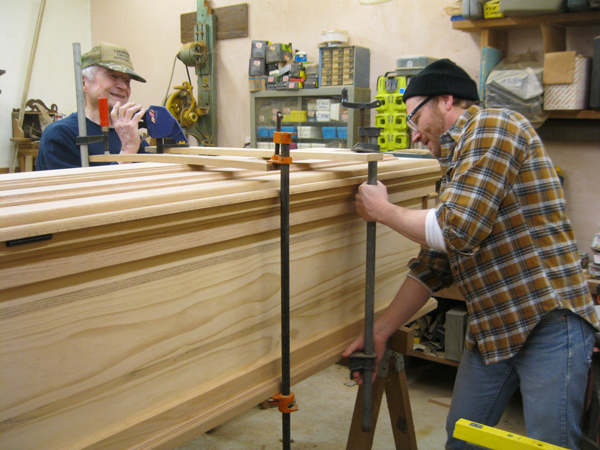 A son building a casket with his father in a work room