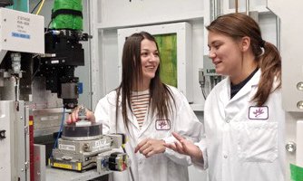 Janna M. Andronowski and a student in white lab coats in a laboratory