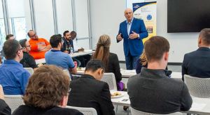 A business executive leads a graduate business class