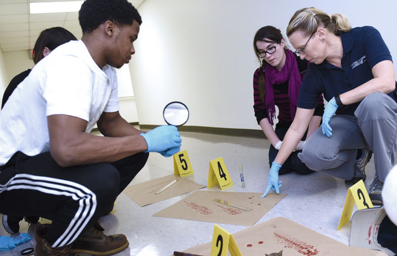 Forensics Lab faculty member Brenda Butler makes a point while analyzing a mock crime scene with students