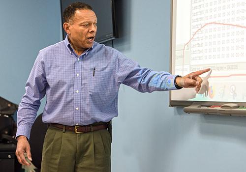 A professor gestures near a whiteboard during a class