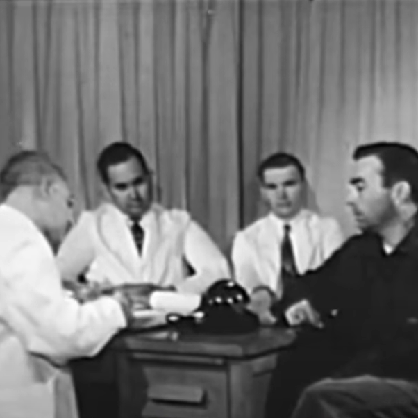 Doctors gathered around a table with a man
