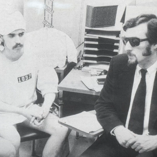 A man in sunglasses seated with a man in a prison uniform