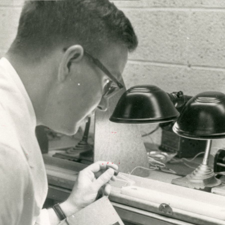 A man peering down into an illuminated tray in a laboratory