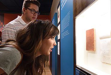 Two people leaning in to examine a museum display