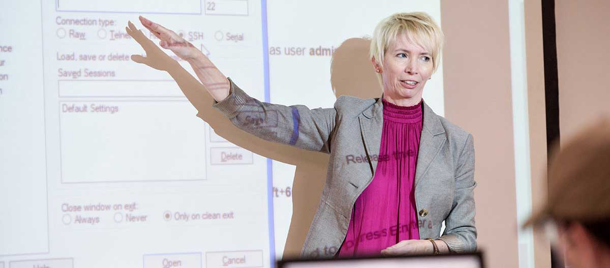 A computer networking professor gestures while leading a class discussion