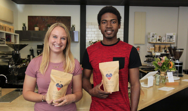 Employees at Akron Coffee Roasters holding bags of Zips 4 Haiti coffee
