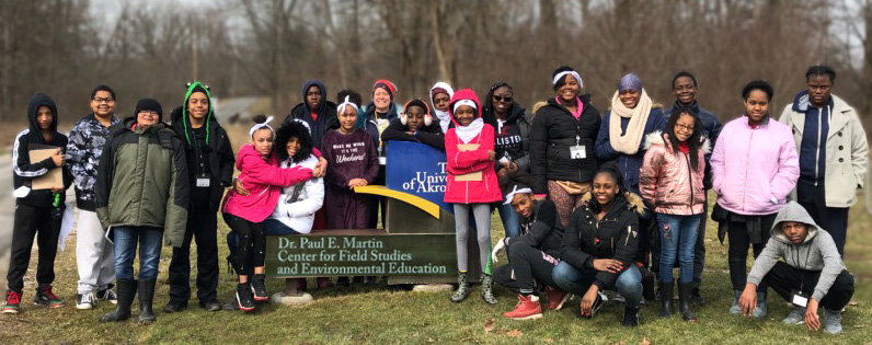 Akron Public School students pose in front of The University of Akron Field Station sign