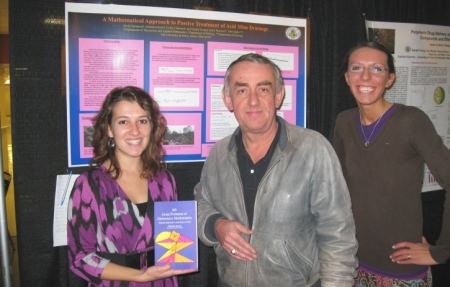 Mathematics students at a conference accept an award for their work.