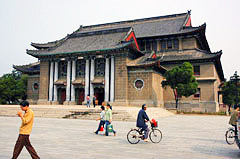 People walk and ride bicycles past a building on the Henan University campus