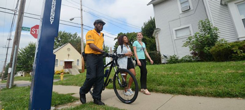 A safety patrol officer escorts two University of Akron students
