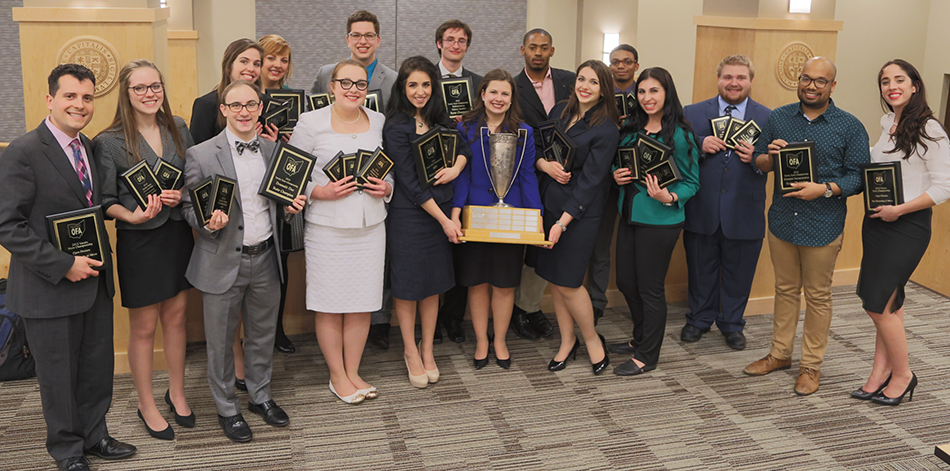 The University of Akron speech and debate team and coaches, with their first state title trophy from the Ohio Foresnsic Association State Championship Tournament.