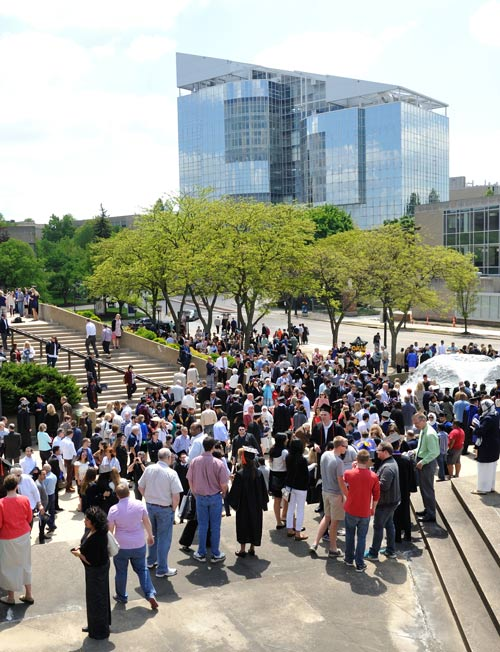 Student gather after commencement on a plaza with the iconic polymer building in the background