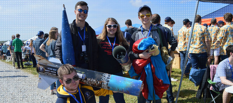 Members of the college's student rocket design team and the rocket they designed