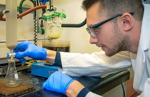 A student research conducts an experiment in a lab at UA