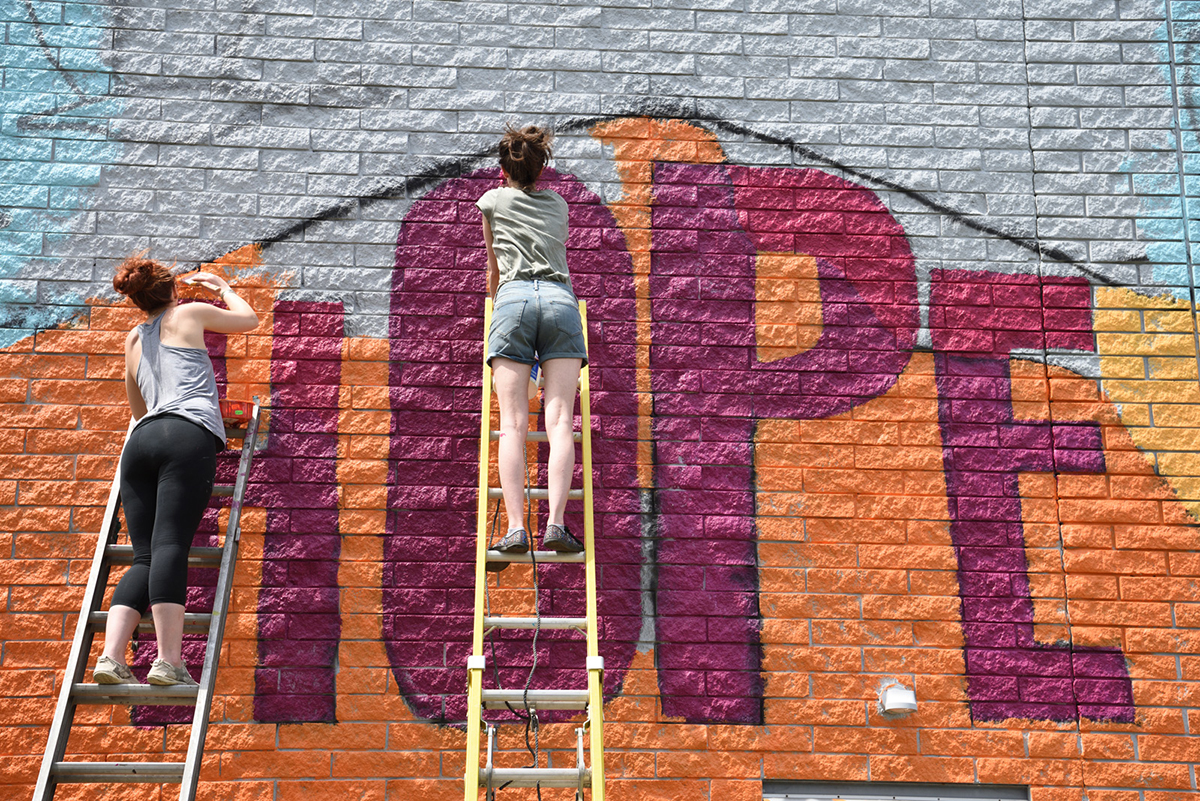 Students painting a outside wall in the city of akron