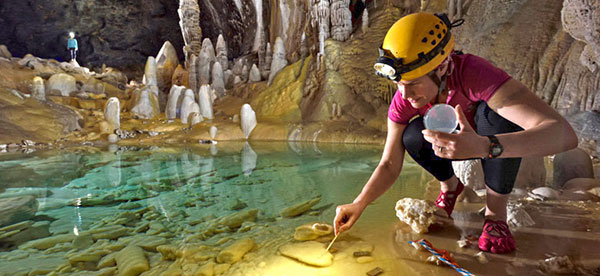 A researcher beside a pool of water in a cave