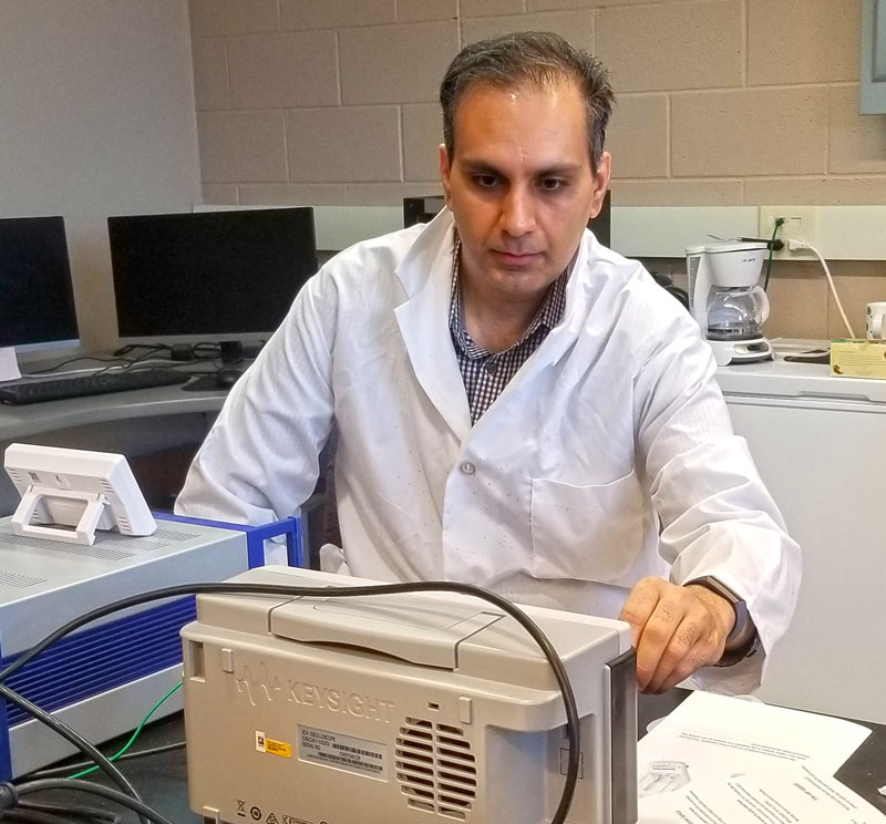 A researcher in a white coat working in a laboratory at The University of Akron