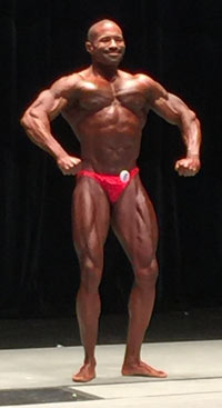 A bodybuilder on a stage holding a pose