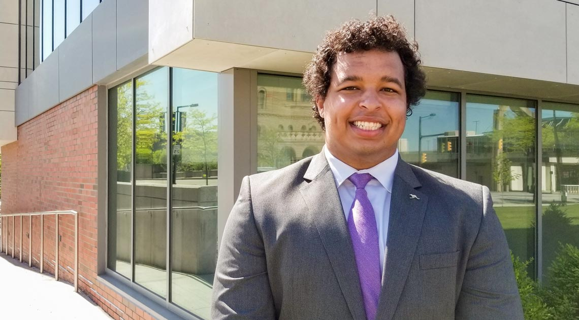 Maxwell Nixon is the inaugural recipient of the Charles Schwab Foundation Endowed Scholarship for Financial Planning at             The University of Akron, stands on campus on a sunny day
