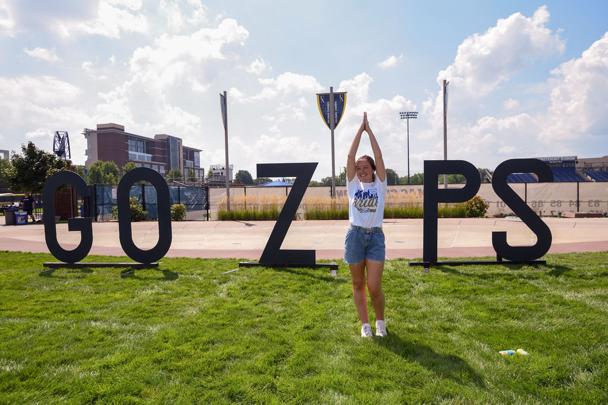 A student makes the I in GO ZIPS, a cutout on Coleman Common