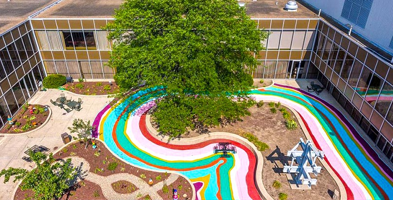 An aerial view of courtyard brightened by a painted rainbow on its sidewalks
