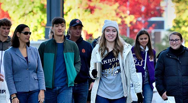 A student leads a tour of campus for students and parents