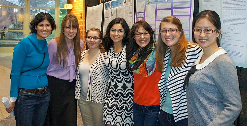 Seven women from the Math Department at a poster session.