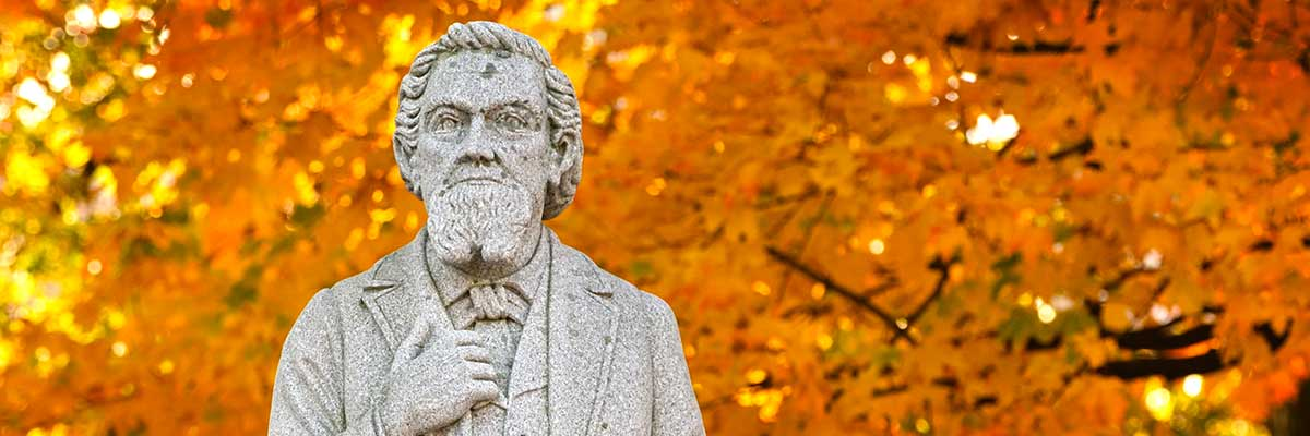 A statue of the University's founder with yellow leaves behind him