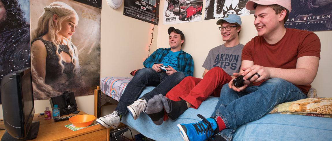 Three students playing a video game in a residence hall at The University of Akron