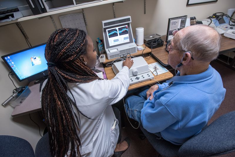 A student in the doctor of audiology program at The University of Akron assists a patient