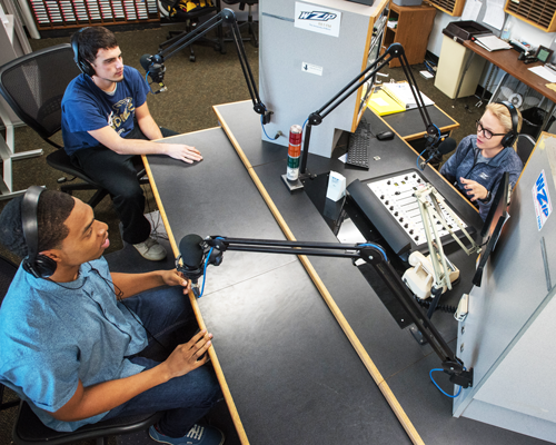 Three student DJs working in the UA WZIP radio studio during an on-air production.
